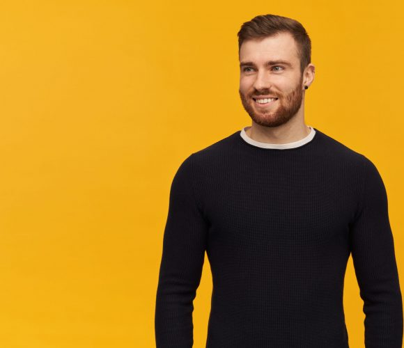 Smiling handsome young man with beard in black longsleeve standing and looking away to the side over yellow background